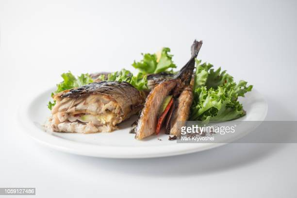 baked mackerel with green salad and lemon on white plate - mackerel stock pictures, royalty-free photos & images
