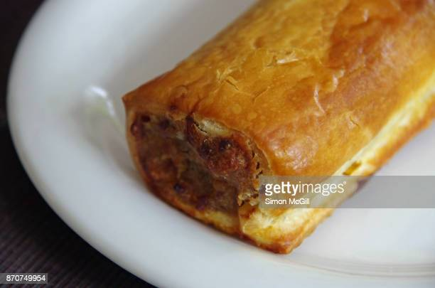 Baked meat sausage roll on a round white plate