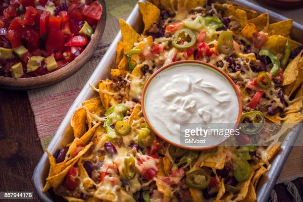 baked nachos tortilla chips with salsa, minced meat and jalapenos - nachos stock photos and pictures