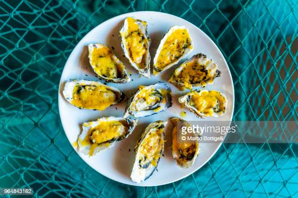 Baked oysters plate on a blue fishing net