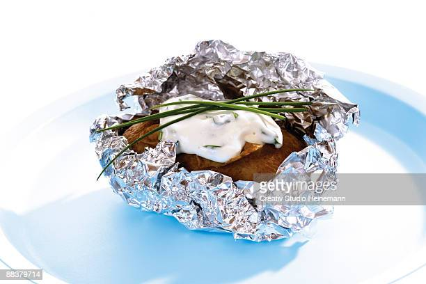 Baked potato with curd cheese in plate, close-up