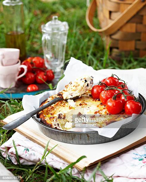 Baked ricotta with vine tomatoes on book outdoors