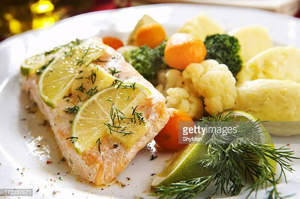 Baked salmon dish with assorted vegetables and lemon