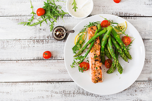 Baked salmon garnished with asparagus and tomatoes with herbs 530418242