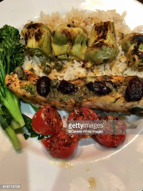 Baked Salmon slices on a plate with vegetables and rice