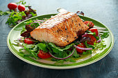Baked salmon steak with tomato, onion, mix of green leaves salad in a plate. healthy food