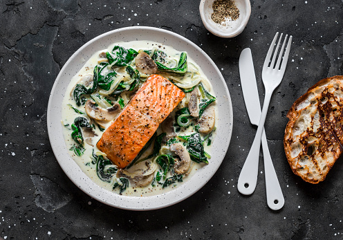 Baked salmon with creamy spinach mushrooms sauce on a dark background, top view. Salmon florentine 1163726141