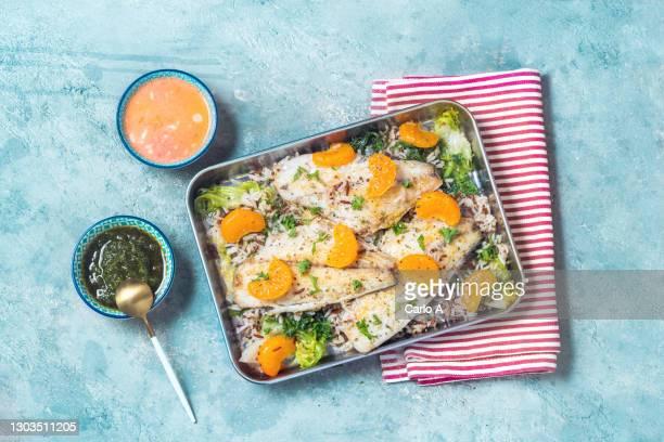 baked sea bass fillet with tangerines and kale - arroz integral - fotografias e filmes do acervo
