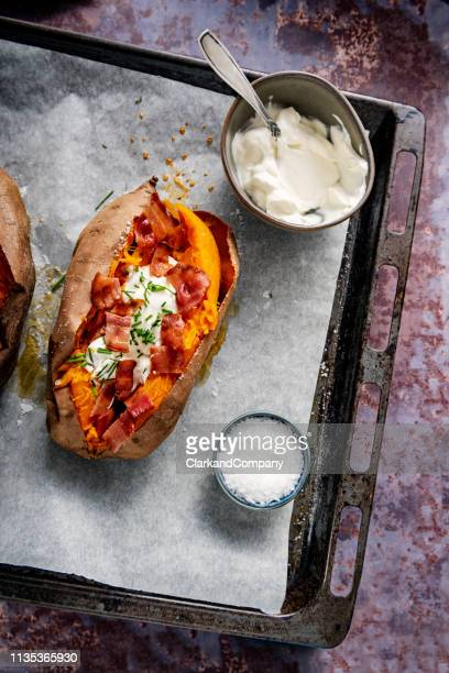 baked sweet potato with sour cream, chives and bacon. - sweet potato stock pictures, royalty-free photos & images