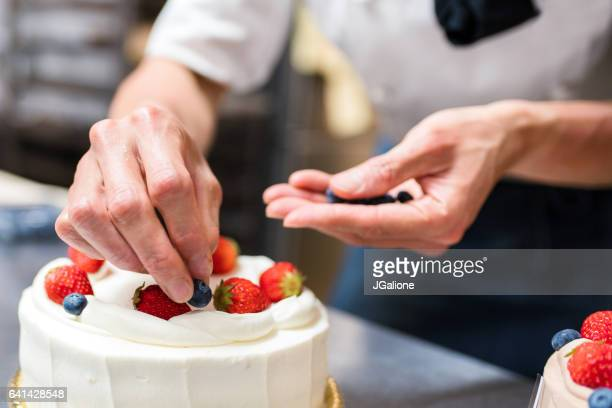 baker adding blueberries to a cake - decorating a cake stock pictures, royalty-free photos & images