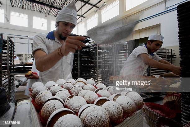 A baker adds powdered sugar to sweet bread at La Ideal bakery in Mexico City Mexico on Thursday Oct 24 2013 The pan de muerto or bread of the dead is...