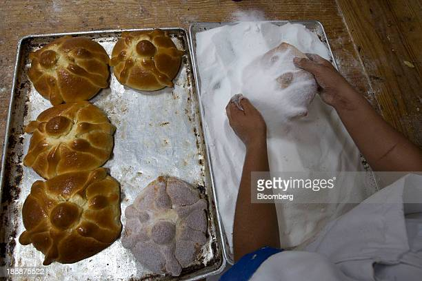 A baker adds sugar to loaves of pan de muerto at La Ideal bakery in Mexico City Mexico on Thursday Oct 24 2013 The pan de muerto or bread of the dead...