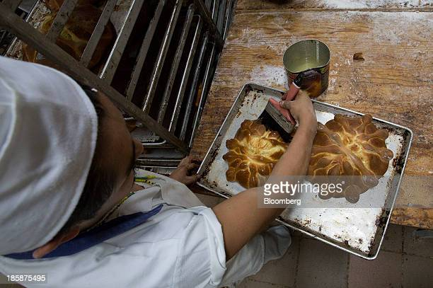 A baker adds syrup to loaves of pan de muerto at La Ideal bakery in Mexico City Mexico on Thursday Oct 24 2013 The pan de muerto or bread of the dead...