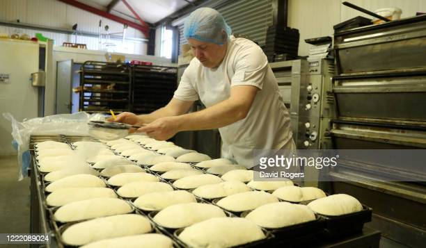 Baker, Andy Collins, sprinkles flour as he prepares traditional loaves for the oven at Whittlebury Bakery on April 30, 2020 in Whittlebury, England....