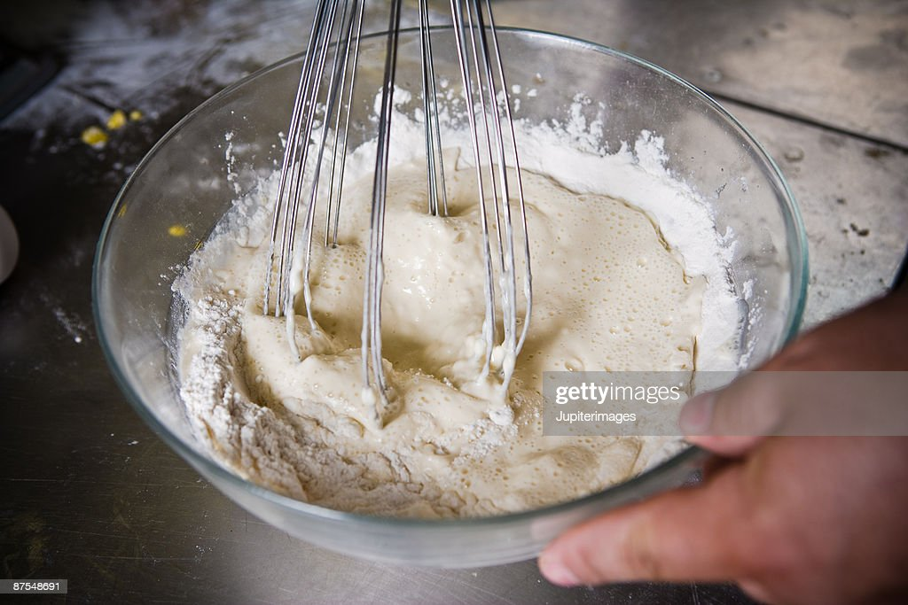 Baker beating eggs and flour in glass bowl : Stock Photo