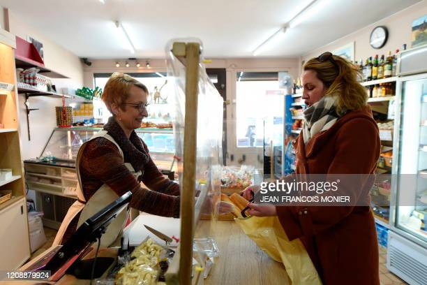 A baker behind a protective plastic film serves a customer in Chassant western France on April 1 on the sixteenth day of a lockdown aimed at curbing...