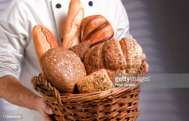 baker carrying basket of freshly baked bread - bread stock pictures, royalty-free photos & images
