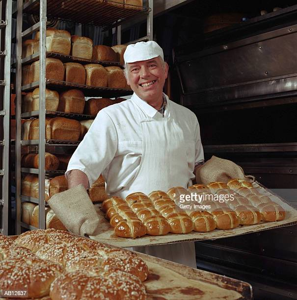 baker carrying hot cross buns - hot cross bun stock pictures, royalty-free photos & images