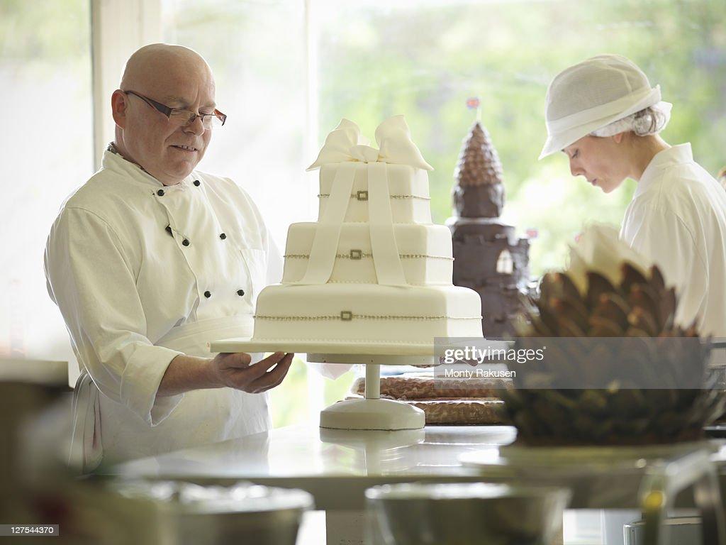 Baker checking decorative wedding cake : Stock Photo