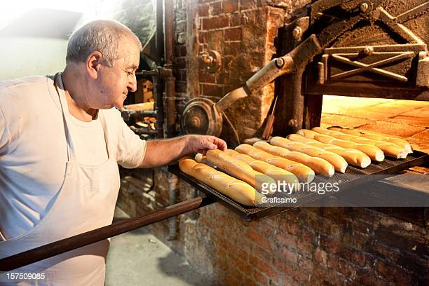 Baker controlling bread in antique bakery
