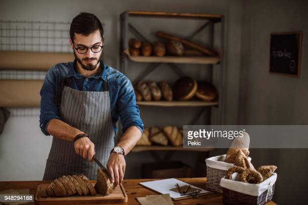 baker cutting fresh bread - gluten free bread stock pictures, royalty-free photos & images