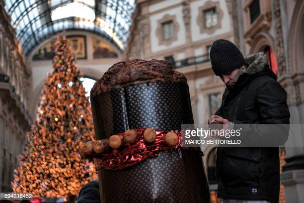 A baker decorates a giant Panettone on December 17 2017 in the Vittorio Emanuele II gallery in Milan The Panettone a typical brioche of Christmas in...