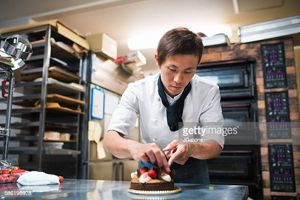 baker decorating a cake - jgalione stock pictures, royalty-free photos & images