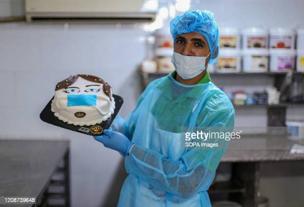 Baker displays a donut-shaped cake wearing a face mask during the corona virus pandemic. Palestinian bakers make different shapes of cakes relating...