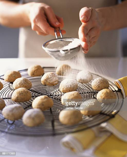 Baker dusting cookies with powdered sugar