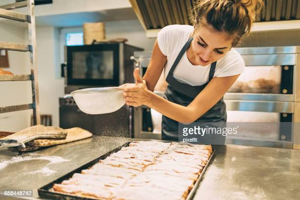 baker dusting the pastry with powder sugar - icing sugar stock pictures, royalty-free photos & images
