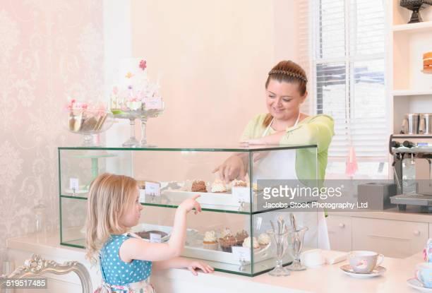 Baker helping girl choose pastries in bakery