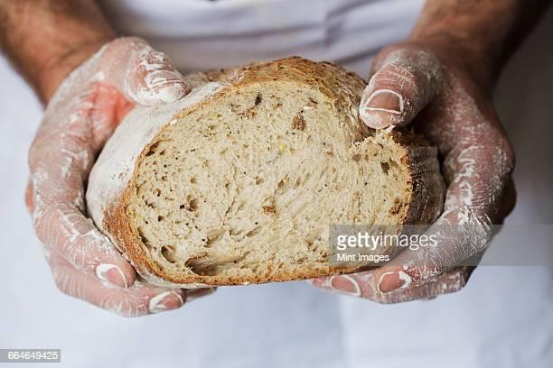 Baker holding a freshly baked loaf of bread.
