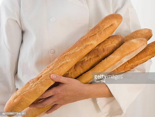 Baker holding baguettes, close-up