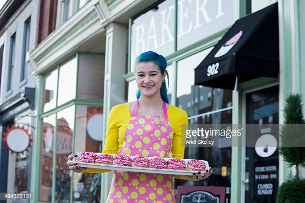 Baker holding donuts outside shop