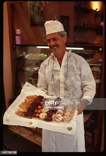 Baker Holding Tray of Desserts