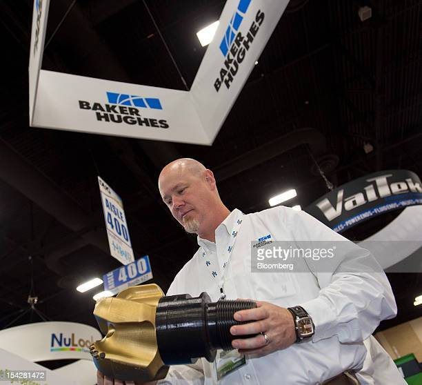 Baker Hughes Inc representative Jason Mailand holds a three dimensional copy of a Baker Hughes Talon drill bit at the DUG Eagle Ford Conference...