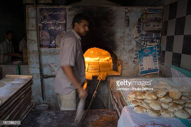 Baker in his traditional oven making bread and chewing qat at the same time in Al Mahwit, Al Mahwit, Yemen. Yemen is the second poorest Arab state...