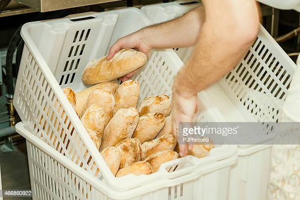 Baker inserting cooked bread on basket