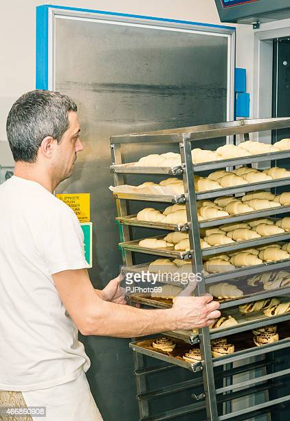Baker inserting uncooked croissants in leavening chamber