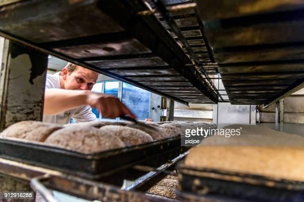 Bäcker bereitet Brot Ofen
