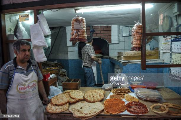 A baker makes breads for fasting time at the Antakya historical bazaar on June 5 2017 in Hatay / AFP PHOTO / OZAN KOSE