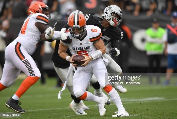 Baker Mayfield of the Cleveland Browns fights to break the tackle of Arden Key of the Oakland Raiders during the third quarter of their NFL football...