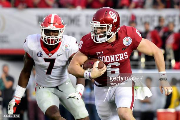 Baker Mayfield of the Oklahoma Sooners runs away from Lorenzo Carter of the Georgia Bulldogs during the third quarter in the 2018 College Football...