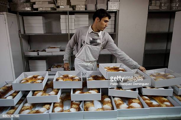 A baker places the 'Roscones de Reyes' on top of a table to cool down after baking at the Antigua Pasteleria del Pozo ahead of the Three Kings Day on...