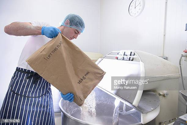 Baker pouring flour from sack into mixer