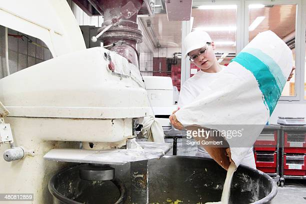 baker pouring flour into mixer - sigrid gombert imagens e fotografias de stock