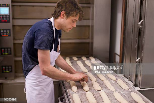 Baker prepares baguettes for the oven