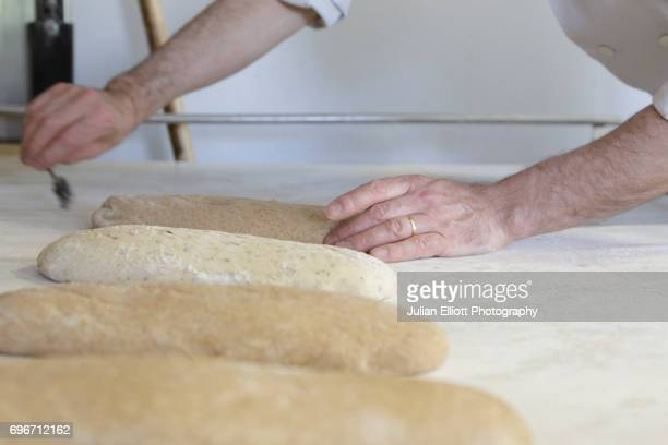 a baker prepares bread for the oven. - chedigny photos et images de collection