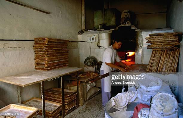 A baker prepares khobbez, flat bread, in a gas fired oven.