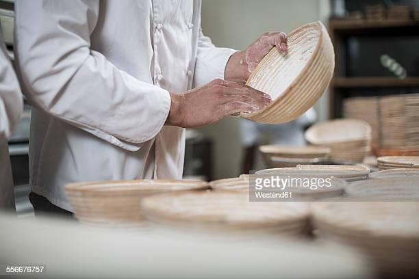 Baker preparing bread pans for baking bread